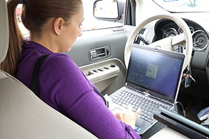 APS caseworker working on her laptop inside a car
