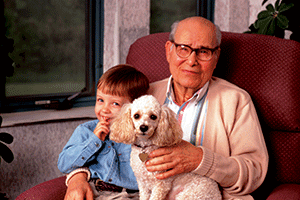 A Elderly gentleman sitting on the couch with his young grandson and a white dog