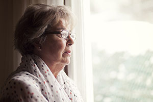 An elderly lady looking out of the window