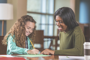 A caregiver helping a young adult in a classroom setting