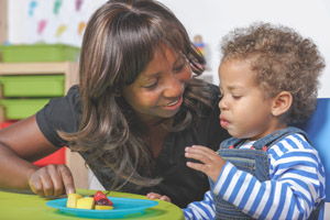 A caregiver looks on similing at a toddler