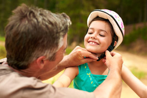 A caregiver putting on a bike helmet on a child