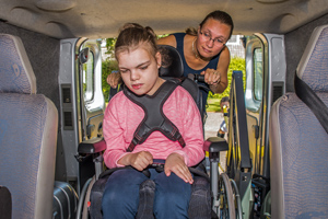 An adult helping a child in a wheel chair inside a car