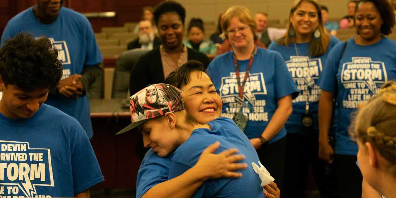 Volunteer hugging former foster child at adoption ceremony.