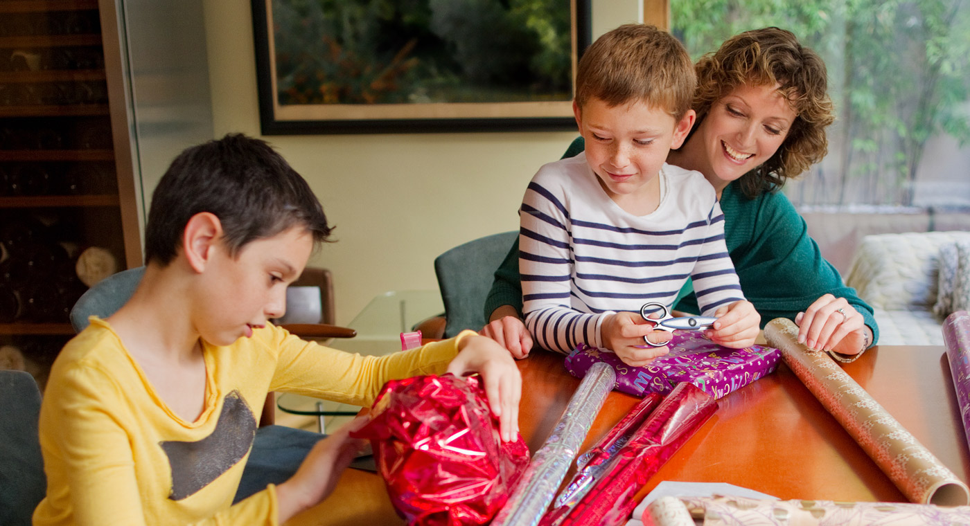 lady helping two boys wrap presents
