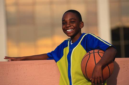 boy smiling and holding a basket ball