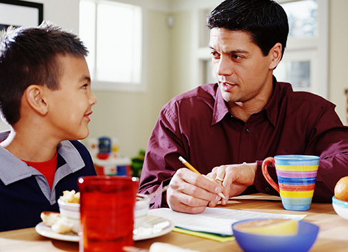 Male adult helping a child with homework